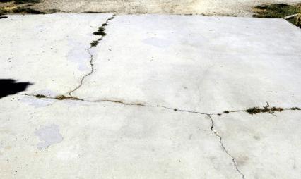 Concrete driveway that has cracks running through it